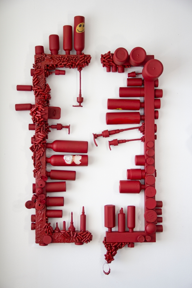a sculptural piece made out of used plastic bottles, pills, jewelry boxes arranged on rectangular frames. A commentary on contemporary dependency on consumption and luxury goods